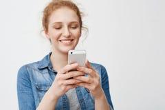 Retrato de la muchacha encantadora positiva del pelirrojo con el peinado del bollo que sonríe sensual mientras que lleva a cabo s Imagenes de archivo