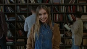 Retrato de la muchacha encantadora sonriente en biblioteca almacen de video