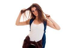 Retrato de la muchacha enojada joven del estudiante con la mochila azul aislada en el fondo blanco Fotos de archivo libres de regalías