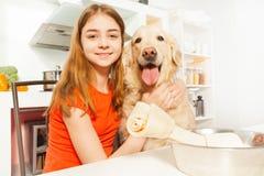 Retrato de la muchacha feliz con su animal doméstico en la cocina Fotos de archivo