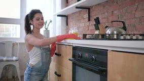 Retrato de la muchacha feliz del ama de casa en los guantes de goma durante la limpieza general de la cocina y del quehacer domés almacen de metraje de vídeo