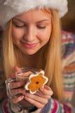Retrato de la muchacha feliz en el sombrero de santa con la taza de chocolate caliente Foto de archivo