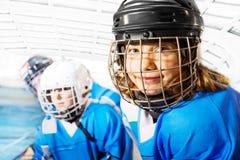 Retrato de la muchacha feliz en uniforme del hockey sobre hielo foto de archivo