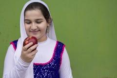 Retrato de la muchacha feliz hermosa adolescente con la manzana roja en la derecha Imagenes de archivo