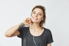 Retrato de la muchacha feliz hermosa joven que sonríe mirando música que escucha de la cámara en auriculares sobre el fondo blanc Fotografía de archivo libre de regalías