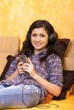 Retrato de la muchacha feliz hermosa que miente en una cama con los auriculares Fotografía de archivo