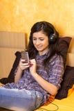 Retrato de la muchacha feliz hermosa que miente en una cama con los auriculares Foto de archivo