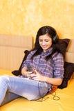 Retrato de la muchacha feliz hermosa que miente en una cama con los auriculares Imágenes de archivo libres de regalías