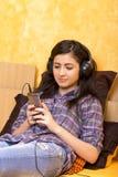 Retrato de la muchacha feliz hermosa que miente en una cama con los auriculares Imagenes de archivo