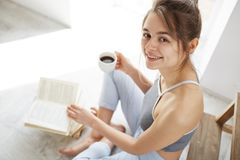 Retrato de la muchacha feliz hermosa que sonríe mirando la cámara que sostiene la taza de café que se sienta en piso con el libro Foto de archivo
