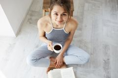 Retrato de la muchacha feliz hermosa que sonríe mirando la cámara que sostiene la taza de café que se sienta en piso con el libro Imagen de archivo libre de regalías