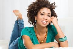 Mujer joven que miente en el sofá Imágenes de archivo libres de regalías