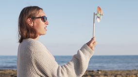 Retrato de la muchacha feliz linda que se divierte con el molinillo de viento en la playa metrajes