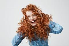 Retrato de la muchacha feliz linda que sonríe tocando su pelo rojo rizado sobre el fondo blanco Imagen de archivo