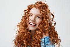 Retrato de la muchacha feliz linda que sonríe tocando su pelo rojo rizado sobre el fondo blanco Imagen de archivo libre de regalías