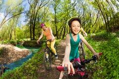 Retrato de la muchacha feliz que monta su bici en el parque Imágenes de archivo libres de regalías