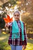 Retrato de la muchacha feliz que muestra la hoja del otoño en el parque Imagen de archivo