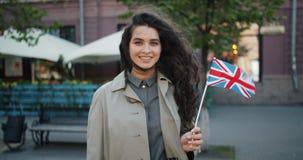 Retrato de la muchacha feliz que se coloca al aire libre con la bandera británica que sonríe en día ventoso almacen de video