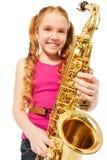 Retrato de la muchacha feliz que toca el saxofón del alto Imágenes de archivo libres de regalías