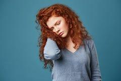 Retrato de la muchacha frustrada infeliz con el pelo ondulado rojo y las pecas que llevan a cabo la mano en pelo con los ojos cer Imagenes de archivo