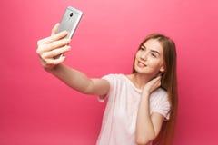 Retrato de la muchacha hermosa alegre, fotografiado, tomando el selfie, mirando en el teléfono, bastante divertido, en backgroun  fotografía de archivo libre de regalías