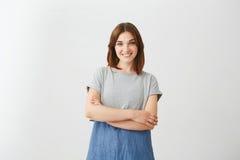 Retrato de la muchacha hermosa alegre joven que sonríe mirando la cámara con los brazos cruzados sobre el fondo blanco Imágenes de archivo libres de regalías