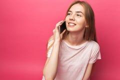 Retrato de la muchacha hermosa alegre que habla en el teléfono, mirando lejos, bastante divertido, en el fondo rosado, haciendo p imagenes de archivo