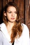 Retrato de la muchacha hermosa cerca de la pared de madera Imagen de archivo