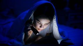 Retrato de la muchacha hermosa con el libro de lectura de la linterna en cama Fotografía de archivo libre de regalías