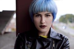 Retrato de la muchacha hermosa con el pelo azul y los labios rojos en un suéter amarillo en el emplazamiento de la obra Foto de archivo libre de regalías