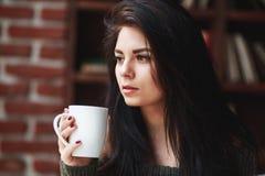 retrato de la muchacha hermosa con el pelo oscuro en un suéter verde con una taza de café o de té en casa Primer Fotos de archivo libres de regalías