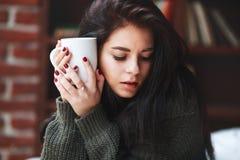 retrato de la muchacha hermosa con el pelo oscuro en un suéter verde con una taza de café o de té en casa Primer Imagen de archivo libre de regalías