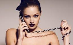 Retrato de la muchacha hermosa con el pelo oscuro que habla por el teléfono Foto de archivo