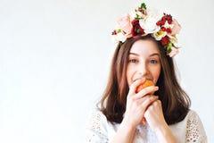 Retrato de la muchacha hermosa con la guirnalda de la flor que come la manzana Fotos de archivo