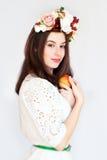 Retrato de la muchacha hermosa con la guirnalda de la flor que sostiene la manzana Fotografía de archivo