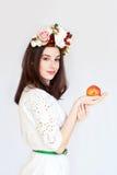 Retrato de la muchacha hermosa con la guirnalda de la flor que sostiene la manzana Imagen de archivo libre de regalías