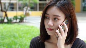 Retrato de la muchacha hermosa de la universidad adulta tailandesa del estudiante que llama el teléfono elegante