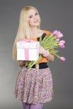 Retrato de la muchacha hermosa del blondie con el regalo y las flores Fotos de archivo