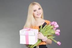 Retrato de la muchacha hermosa del blondie con el regalo y los tulipanes Imagen de archivo