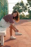 Retrato de la muchacha hermosa del deporte que se sienta en la mirada de los campos de tenis Imagen de archivo libre de regalías