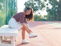 Retrato de la muchacha hermosa del deporte que se sienta en looki de los campos de tenis Fotografía de archivo