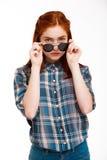 Retrato de la muchacha hermosa del jengibre en gafas de sol sobre el fondo blanco Fotos de archivo libres de regalías