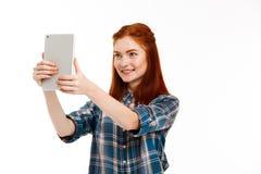 Retrato de la muchacha hermosa del jengibre que hace el selfie sobre el fondo blanco Foto de archivo libre de regalías