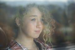 Retrato de la muchacha hermosa del pelirrojo detrás del vidrio con la reflexión Imagen de archivo