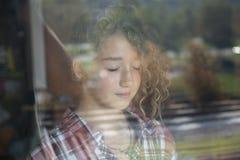 Retrato de la muchacha hermosa del pelirrojo detrás del vidrio con la reflexión Imágenes de archivo libres de regalías
