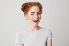 Retrato de la muchacha hermosa del pelirrojo que sonríe mostrando la lengua que guiña mirando la cámara sobre el fondo blanco Fotos de archivo libres de regalías