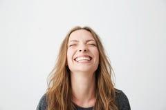 Retrato de la muchacha hermosa emocional joven que ríe con los ojos cerrados sobre el fondo blanco Fotografía de archivo