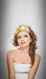 Retrato de la muchacha hermosa en estudio con las rosas amarillas en su pelo y hombros desnudos Mujer joven atractiva con maquill Foto de archivo