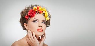 Retrato de la muchacha hermosa en estudio con las rosas amarillas y rojas en su pelo y hombros desnudos Mujer joven atractiva Imagen de archivo libre de regalías