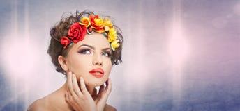 Retrato de la muchacha hermosa en estudio con las rosas amarillas y rojas en su pelo y hombros desnudos Mujer joven atractiva Foto de archivo libre de regalías